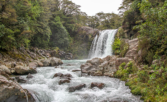 waterfall cascading over a ridge and a fast flowing river meandering across large stones/