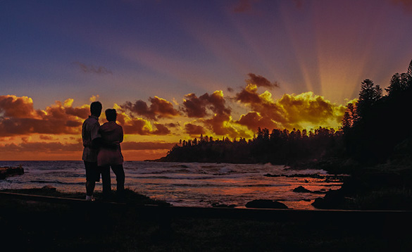 couple stood together looking across sea to the sun rising behind trees/