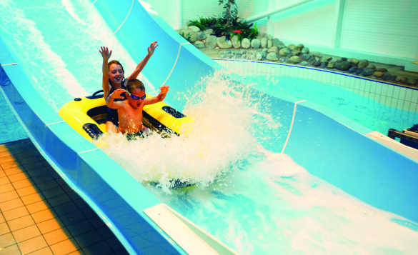 Two children enjoying a waterslide ride at a Butlin's holiday camp/