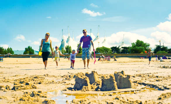Family building sand castles on a sandy beach with the Butlins Skyline Pavillion in the background/