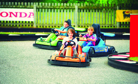 Group of children reding go carts around a course at a Butlins Holiday Camp/