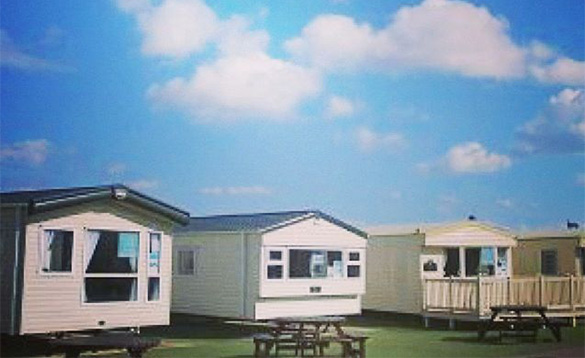 row of four static white caravans with wooden picnic tables in front/
