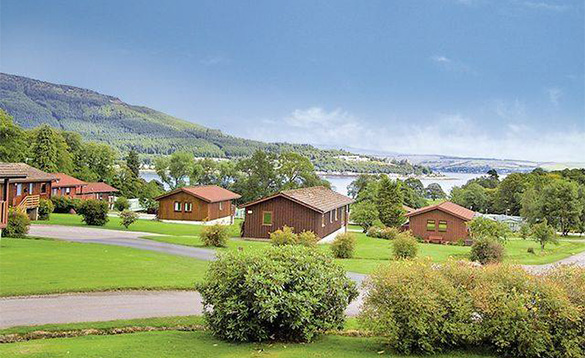group of log cabins on a grassy hillside located amongst bushes with views of lake and mountains/