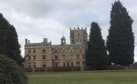 three storey stone built hall with lawns and large trees /