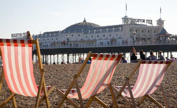Three empty deck chairs on the pebbly beach with Brighton Pier in the background/
