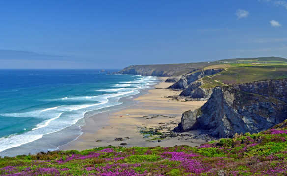 Waves breaking onto a sandy beach along the coastline of Chapel Porth Beach in Cornwall/