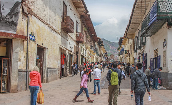 people walking along a busy street in Peru with buildings either side/